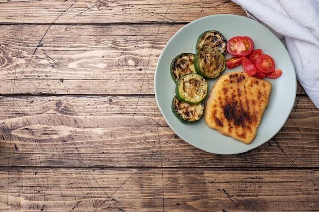 Schnitzel de pollo y calabacín cocinado a la parrilla. tomates frescos en un plato. listo deliciosa cena almuerzo. copia espacio