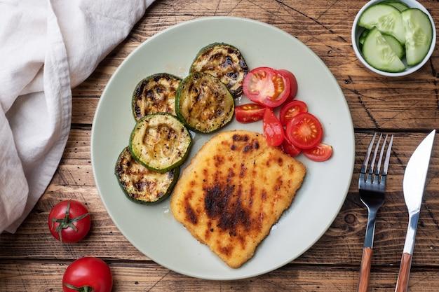 Schnitzel de pollo y calabacín cocinado a la parrilla. tomates frescos en un plato. listo deliciosa cena almuerzo.