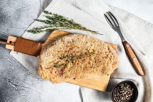 Schnitzel de pollo crudo en pan rallado. fondo gris vista superior