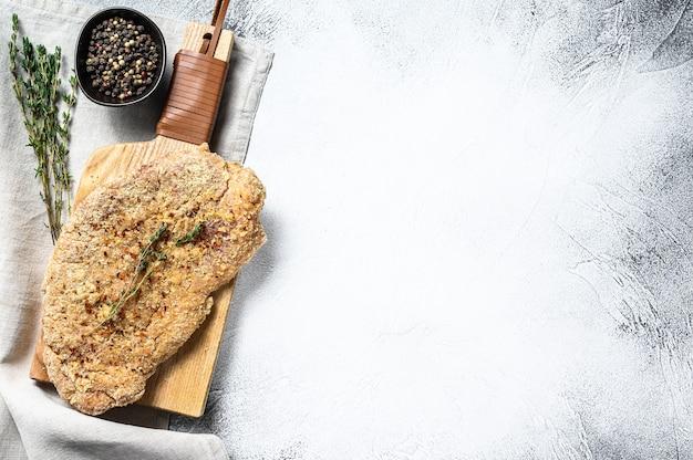 Schnitzel de pollo crudo en pan rallado. fondo gris