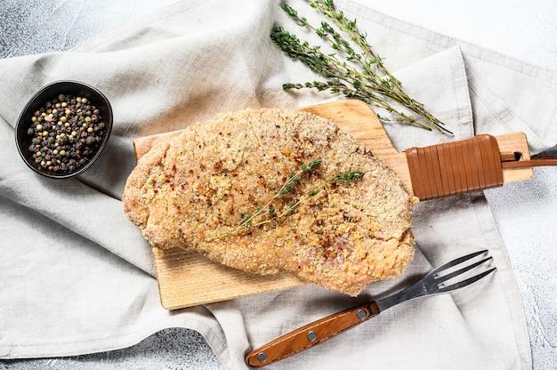Schnitzel de pollo crudo en pan rallado. superficie gris. vista superior