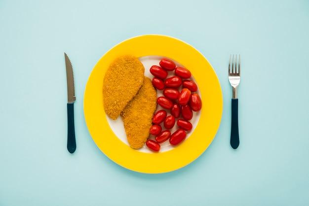 Schnitzel de pollo y tomate pequeño en plato amarillo
