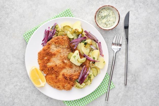 Schnitzel de viena con patatas y cebollas.