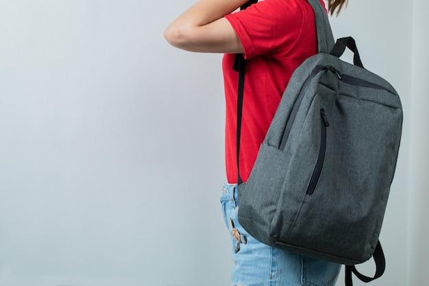 Schoolkid sosteniendo su mochila en los hombros.