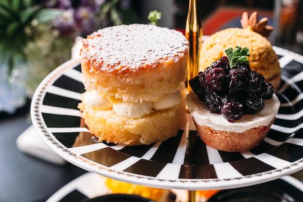 Scone pie cubriendo con glaseado y blueberry mini tart en un plato blanco y negro.