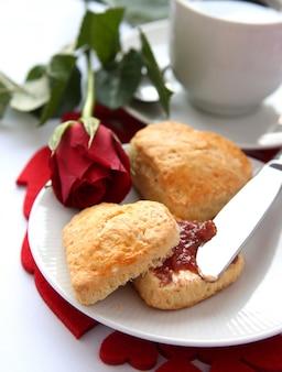 Scones en forma de corazón con mermelada de fresa y una taza de té