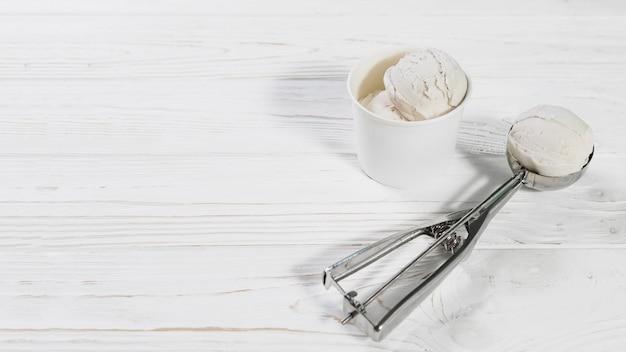 Scoop con bola de helado cerca de la taza