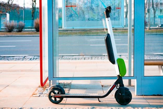Scooter eléctrico está parado cerca de la parada de autobús público. scooter público para alquilar