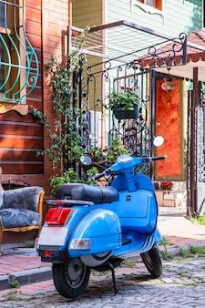 Scooter vintage azul con un edificio, silla y valla, calle peatonal en estambul, turquía