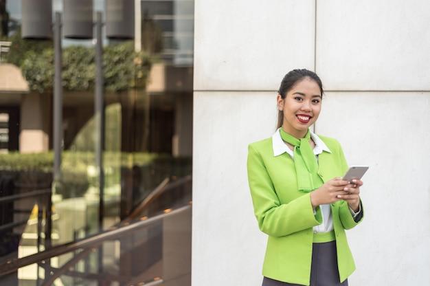 Scort mujer con tableta y teléfono móvil sonriendo