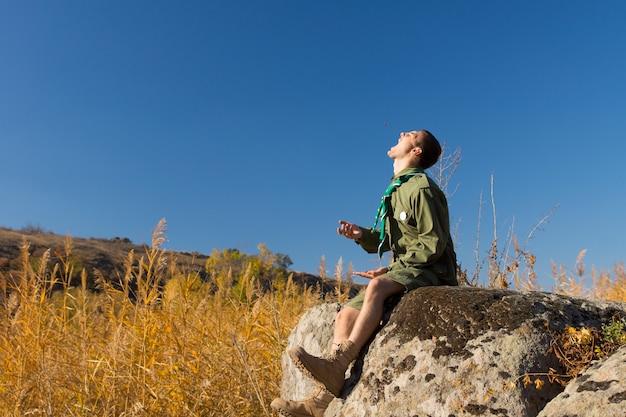Scout o guardabosques en uniforme sentado en una roca en un prado de montaña con la cara hacia el sol gritando mientras disfruta de un día en el desierto