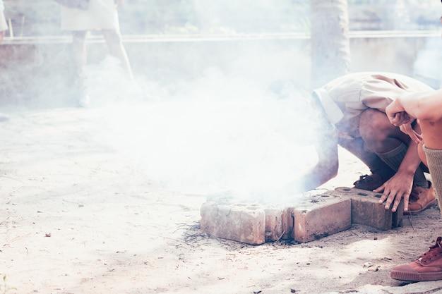 Scouts de uniforme asiático soplan el fuego para cocinar con humo.