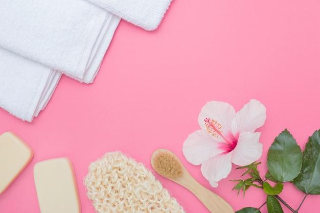 Scrub glove; cepillo; flor hibiscus; jabón y toalla sobre fondo rosa