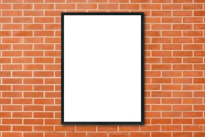 Se burlan del marco del cartel en blanco colgando sobre fondo de pared de ladrillo rojo en la habitación