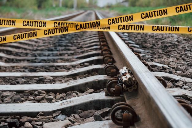 Sea consciente. explosivo peligroso tirado en el ferrocarril. cinta de precaución amarilla al frente