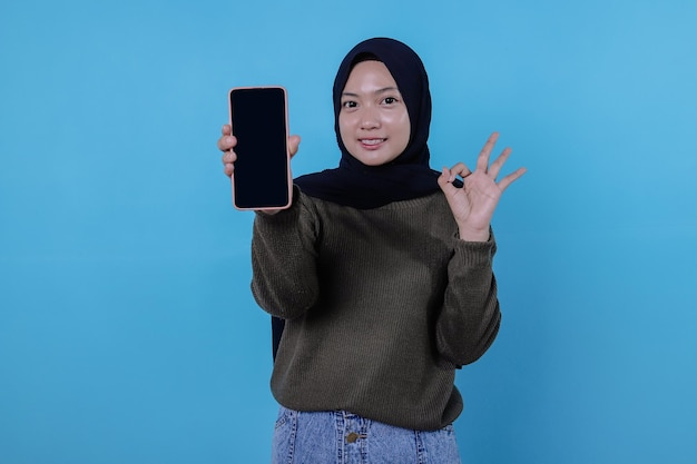 Sea inteligente, compre este dispositivo, retrato de una joven asiática riendo a carcajadas, con hijab apuntando al teléfono inteligente, mostrando la pantalla del dispositivo