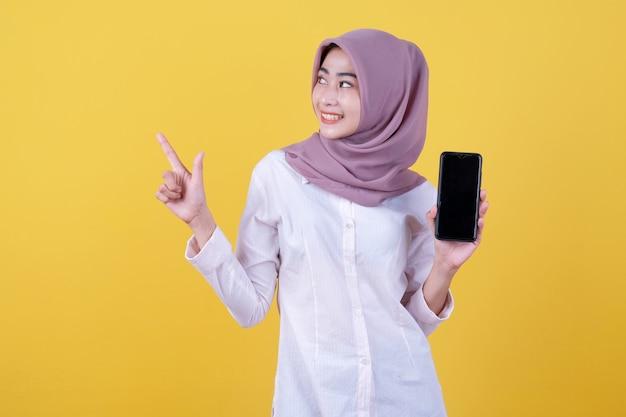 Sea inteligente, compre este dispositivo, retrato de una joven asiática riendo a carcajadas, con hiyab apuntando hacia la parte superior, mostrando la pantalla del dispositivo