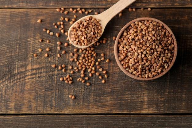 Secar granos de trigo sarraceno en un recipiente de madera con una vista superior de cuchara de madera en la mesa de madera marrón