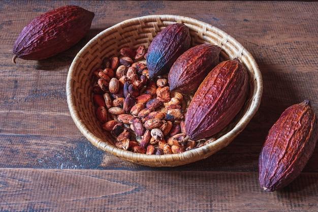 Secar las mazorcas de cacao y los granos de cacao en la canasta sobre fondo de madera