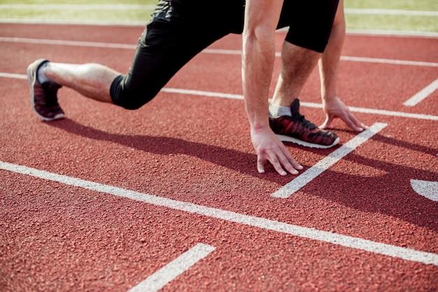 Sección baja de un atleta masculino en la línea de inicio de la pista de carreras