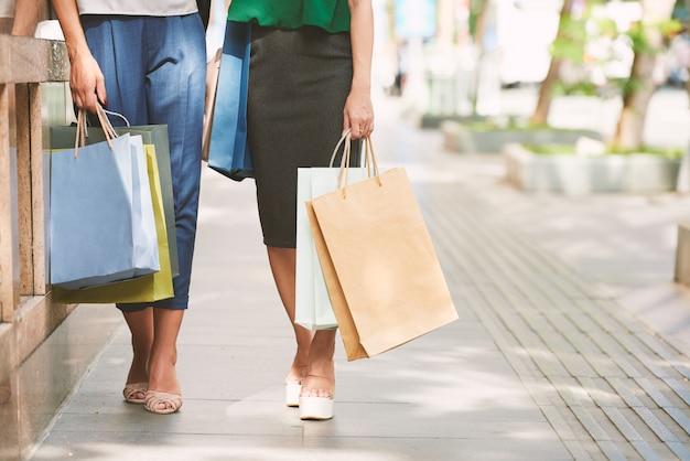 Sección baja de compradores femeninos caminando con bolsas de plástico en la calle