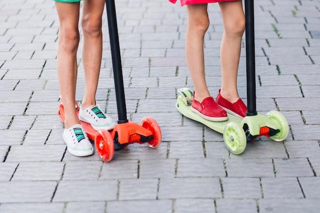 Sección baja de dos chicas de pie en patinete scooter