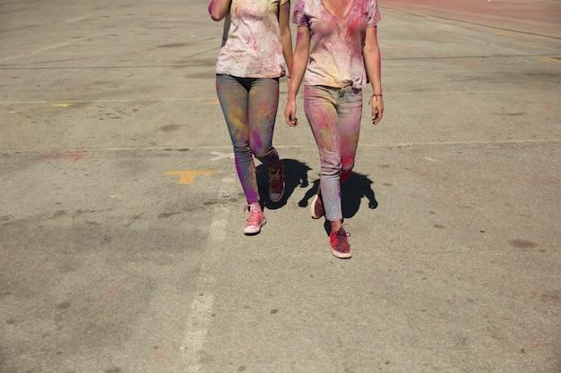 La sección baja de dos mujeres jóvenes se ensucia con el polvo de color holi caminando en la carretera
