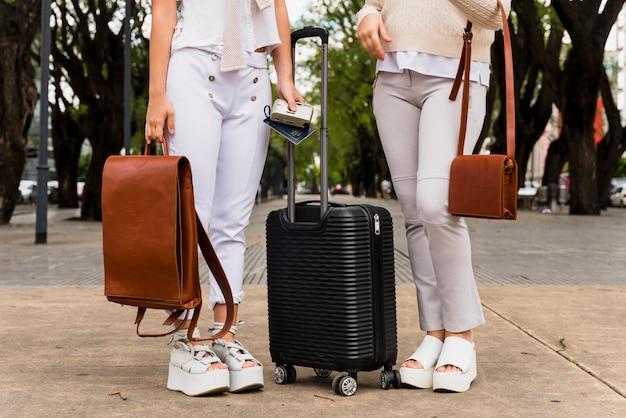 Sección baja de dos mujeres jóvenes de pie con maleta negra y sus bolsas de cuero.