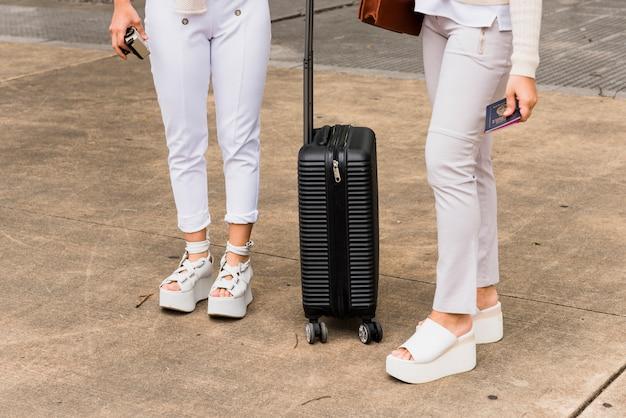 Sección baja de dos mujeres jóvenes de pie con maleta negra.