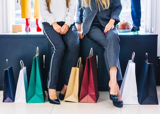 Sección baja de dos mujeres sentadas en la tienda con coloridos bolsos de compras