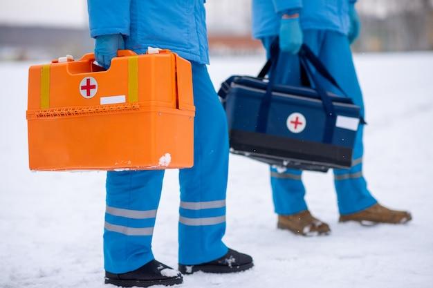 Sección baja de dos paramédicos en uniforme y guantes que llevan botiquines de primeros auxilios mientras van a ayudar y salvar a los enfermos