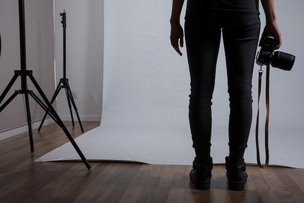 Sección baja de una fotógrafa con cámara en estudio fotográfico