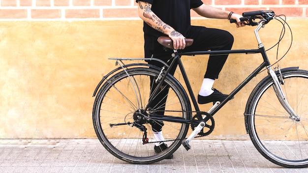 Sección baja de un hombre con bicicleta contra muro pintado y ladrillo.