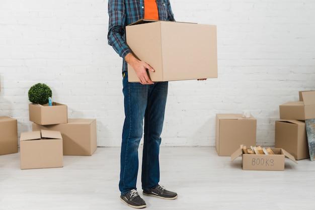 Sección baja de un hombre con caja de cartón en la mano.
