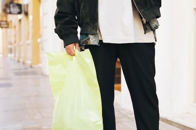 Sección baja de un hombre cargando una bolsa de plástico en la mano.