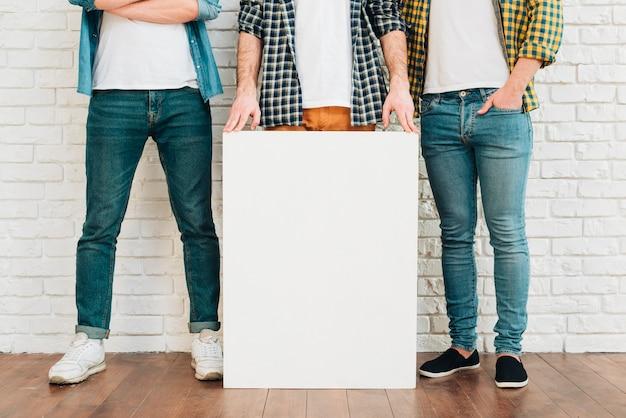 Sección baja del hombre mostrando un cartel blanco con sus amigos.