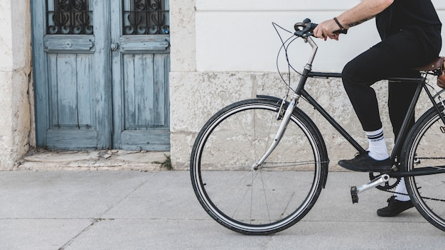 Sección baja de un hombre que monta la bicicleta en la calle.