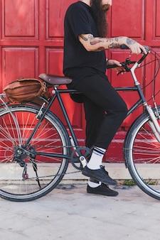 Sección baja de un hombre sentado con bicicleta delante de la puerta.