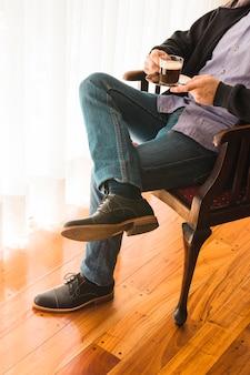 Sección baja de un hombre sentado en una silla con una taza de café en la mano