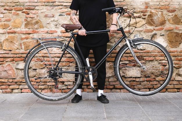 Sección baja de un hombre sosteniendo bicicleta con sus dos manos.