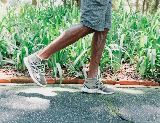 Sección baja de un joven atleta masculino trotando en el jardín