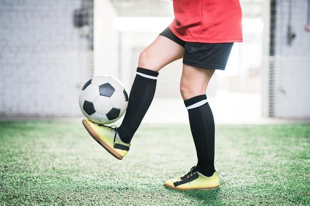 Sección baja de la joven jugadora de fútbol con balón de fútbol sobre pie de pie en campo verde durante el entrenamiento