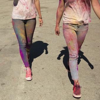 Sección baja de un lío de mujeres con holi color caminando en la carretera