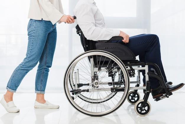 Sección baja de una mujer empujando al hombre sentado en silla de ruedas.