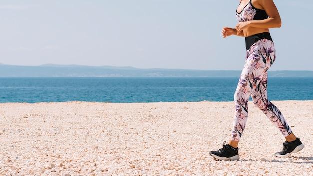 Sección baja de mujer joven deportiva caminando cerca de la playa de gravilla