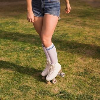 Sección baja de una mujer joven con el patín de ruedas que se coloca en la hierba verde