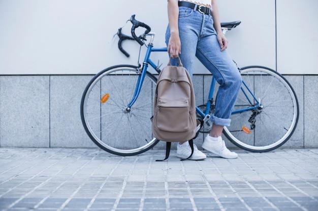 Sección baja de la mujer joven que está parada cerca de la mochila de la tenencia de la bicicleta