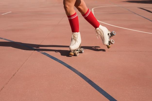 Sección baja de una mujer patinando en una cancha al aire libre