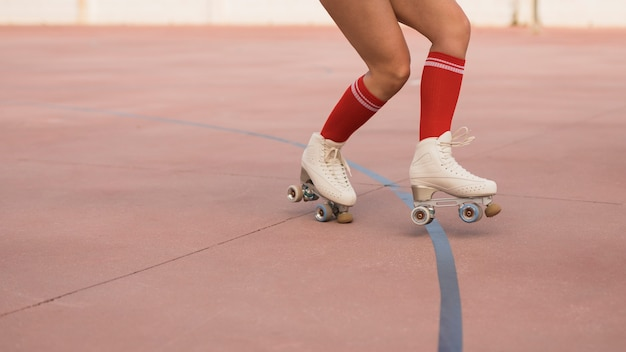 Sección baja de una mujer patinando sobre patines.