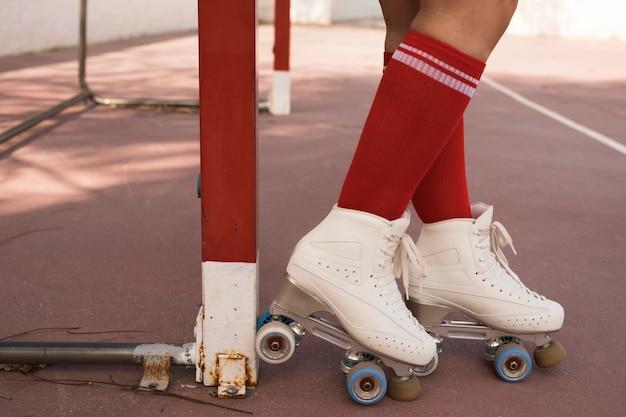 Sección baja de una mujer que lleva un patín de ruedas de pie cerca de la portería de fútbol